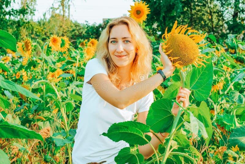 Молодой милый крупный план женщины с солнцецветом на предпосылке поля на летнем времени стоковые изображения