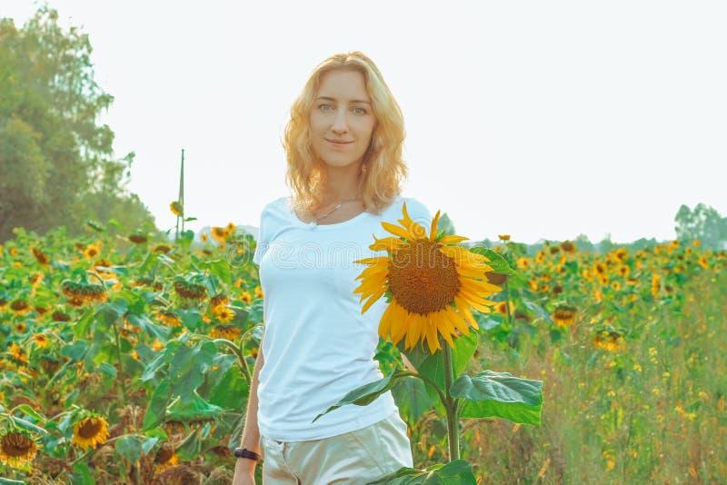 Молодой милый крупный план женщины с солнцецветом на предпосылке поля на летнем времени стоковая фотография rf