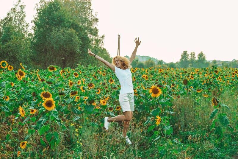 Молодой милый крупный план женщины с солнцецветом на предпосылке поля на летнем времени стоковые фотографии rf