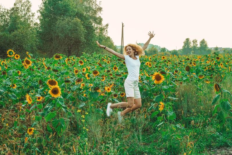 Молодой милый крупный план женщины с солнцецветом на предпосылке поля на летнем времени стоковые изображения rf