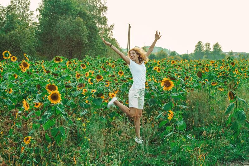 Молодой милый крупный план женщины с солнцецветом на предпосылке поля на летнем времени стоковое изображение
