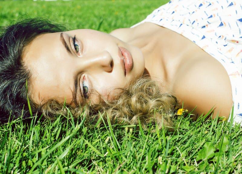 Молодой милый курчавый усмехаться жизнерадостный на зеленой траве, ко стоковое изображение rf