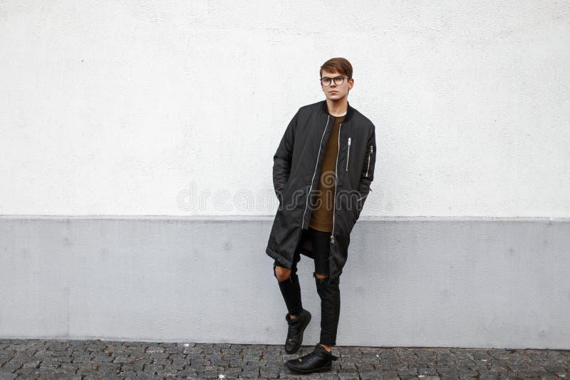 Молодой модельный парень с стеклами в черной куртке и сорванных джинсах стоковые фото