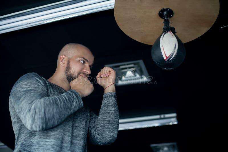 Молодой мужской боксер ударяя грушу на черной предпосылке одетый в форме спорт стоковая фотография