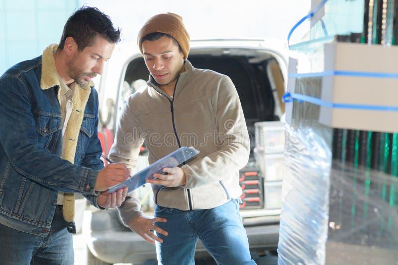 Молодой мужской избавитель давая коробку к человеку стоковые фотографии rf