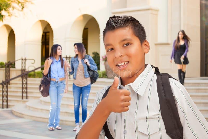 Молодой мужской испанский мальчик студента дает большие пальцы руки вверх на кампусе стоковое фото rf