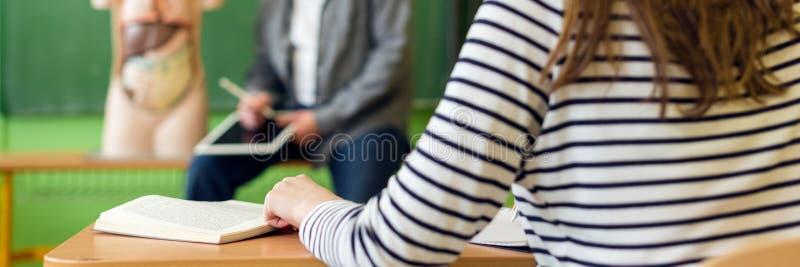 Молодой мужской испанский учитель в уроке биологии, держа цифровую таблетку и уча анатомии человеческого тела, используя искусств стоковые изображения rf