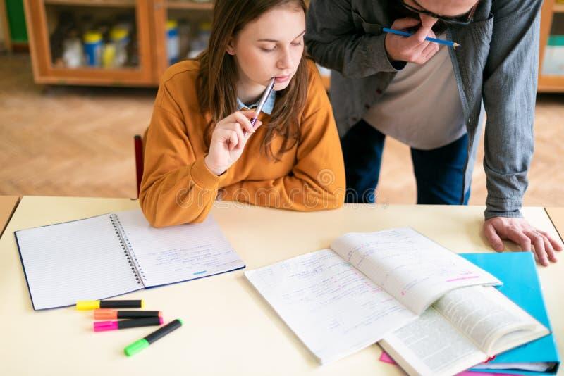 Молодой мужской испанский учитель помогая его студенту в классе химии Образование, обучая стоковое фото rf