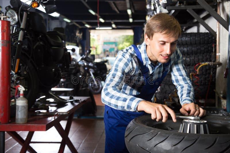 Молодой мужской механик работая в ремонтной мастерской ремонта автомобилей стоковое изображение rf