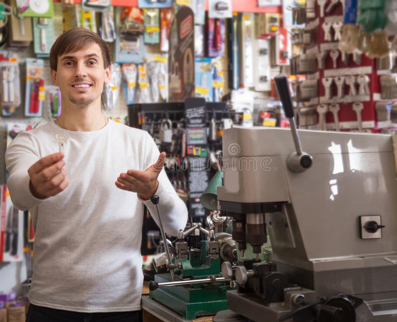 Молодой мужской продавец представляя с ключом стоковое изображение