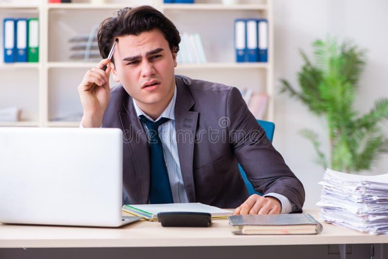 Молодой мужской работник работая в офисе стоковая фотография