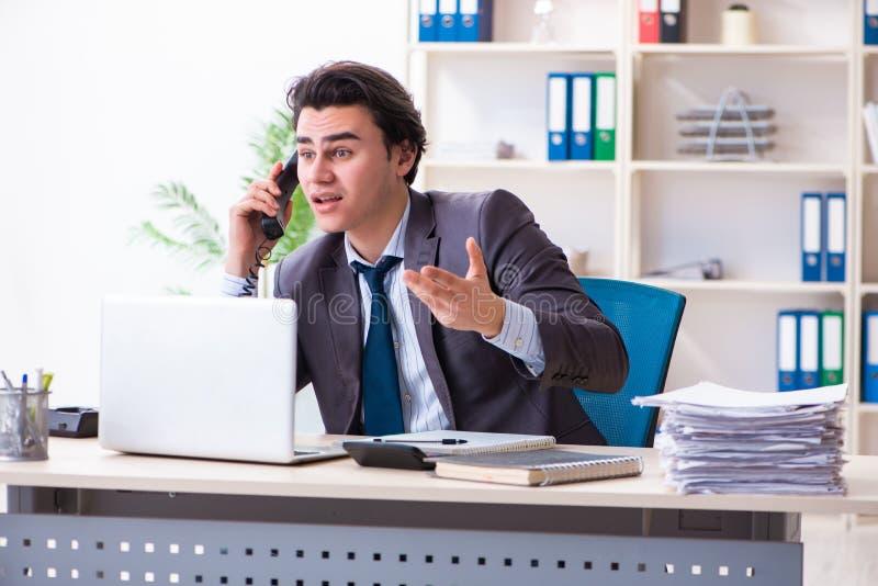 Молодой мужской работник работая в офисе стоковые фотографии rf