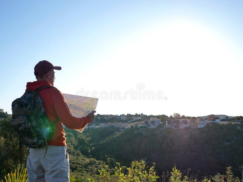 Молодой мужской турист рассматривает карту, стойки на фоне города на холме стоковое изображение rf
