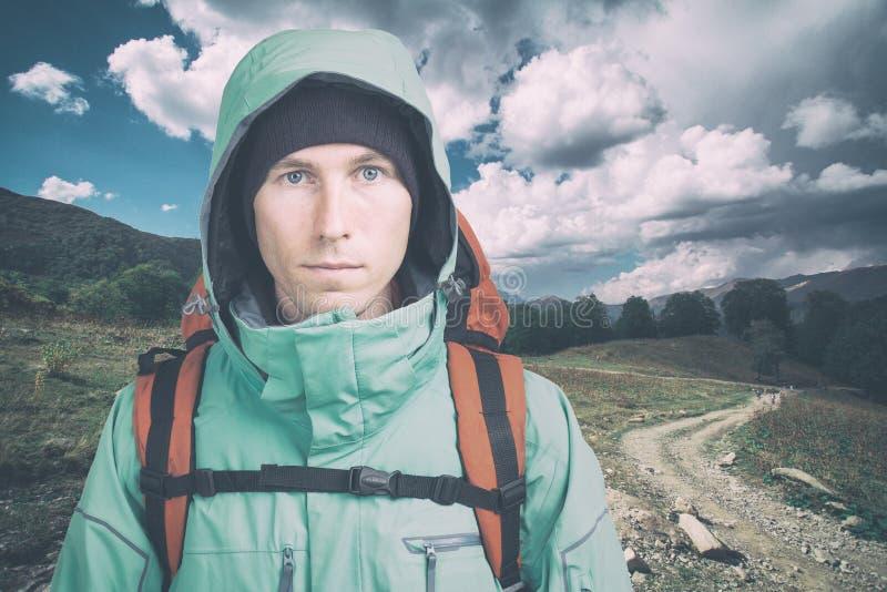 Молодой мужской hiker на пасмурной предпосылке ландшафта смотря камеру r r стоковое изображение rf