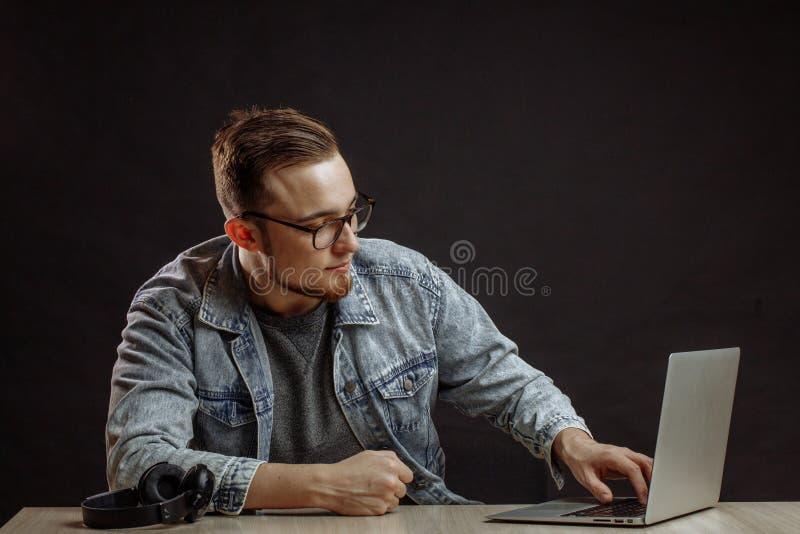Молодой мужчина в стильном обмундировании смотря компьтер-книжку стоковое фото