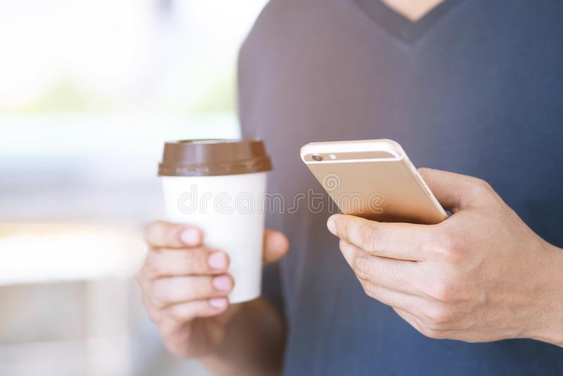 Молодой мужчина используя на стойке сотового телефона в наблюдая сообщении на мобильном телефоне во время бумажного стаканчика уд стоковые фото