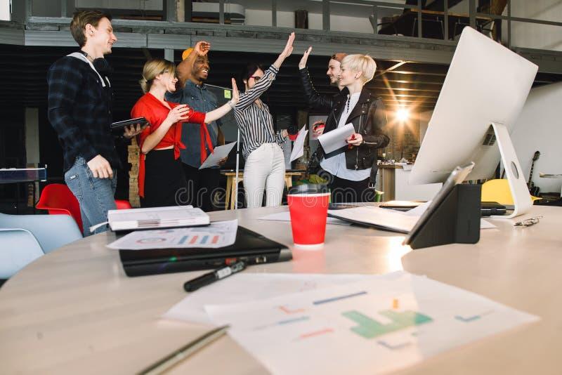 Молодой мужчина и женские коллеги работая с одином другого проекта сотрудничая во время встречи в офисе Группа в составе случайно стоковые изображения