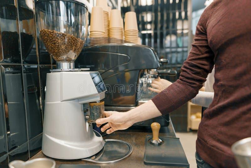 Молодой мужчина barista подготавливая эспрессо на машине кофе, меля кофейных зернах стоковая фотография