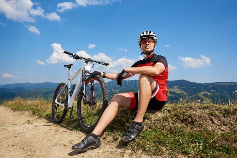 Молодой мышечный велосипедист спортсмена в профессиональном sportswear сидя около его велосипеда стоковые фотографии rf