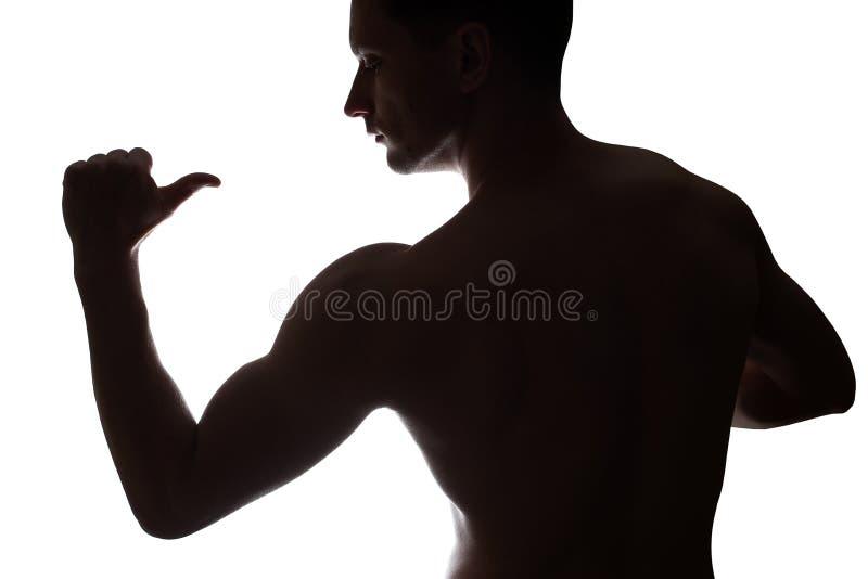 Молодой мышечный культурист демонстрирует его бицепс на белой предпосылке стоковые фотографии rf