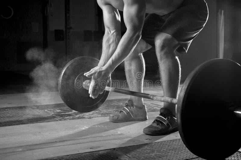 Молодой мышечный человек работая с штангой в спортзале стоковое изображение rf