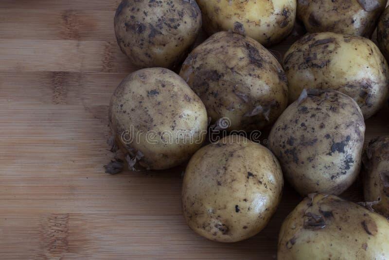 Молодой необработанный конец-вверх картошек на деревянном сборе осени backgroundb стоковые фото