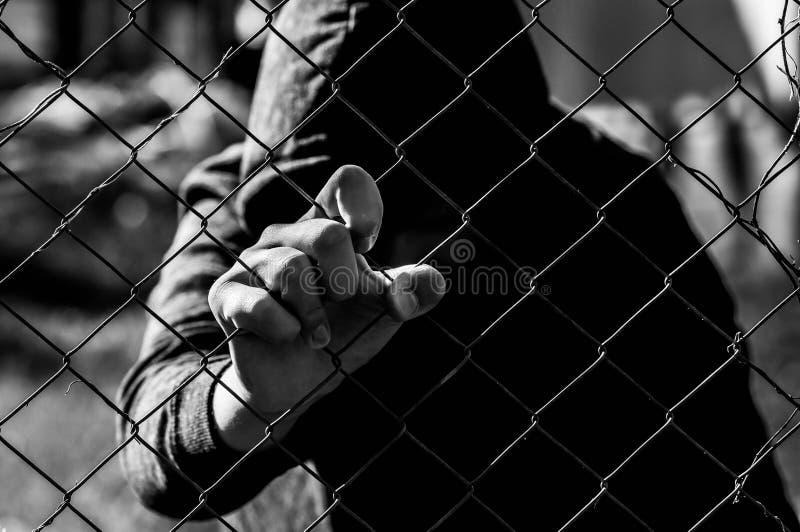 Молодой неопознаваемый подросток держа связанный проволокой сад на исправительном институте в черно-белом стоковые фотографии rf
