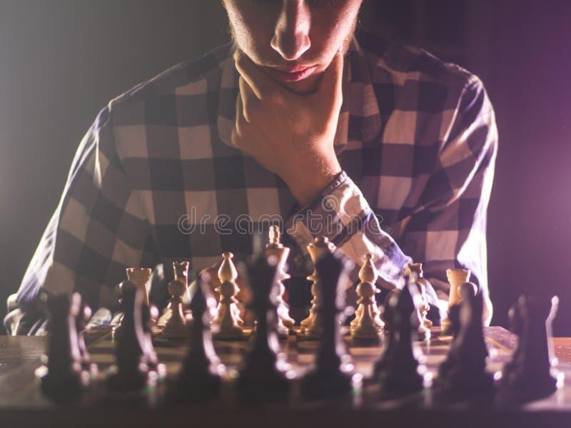 Молодой непознаваемый мужск человек думая около концепции шахматной доски с темной предпосылкой стоковое изображение rf