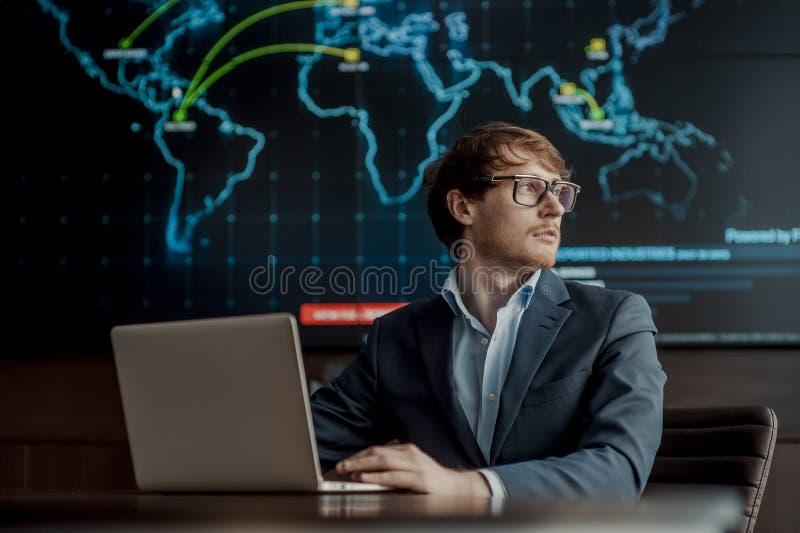Молодой оно бизнесмен инженера с тонким современным алюминиевым ноутбуком в комнате сетевого сервера стоковое изображение