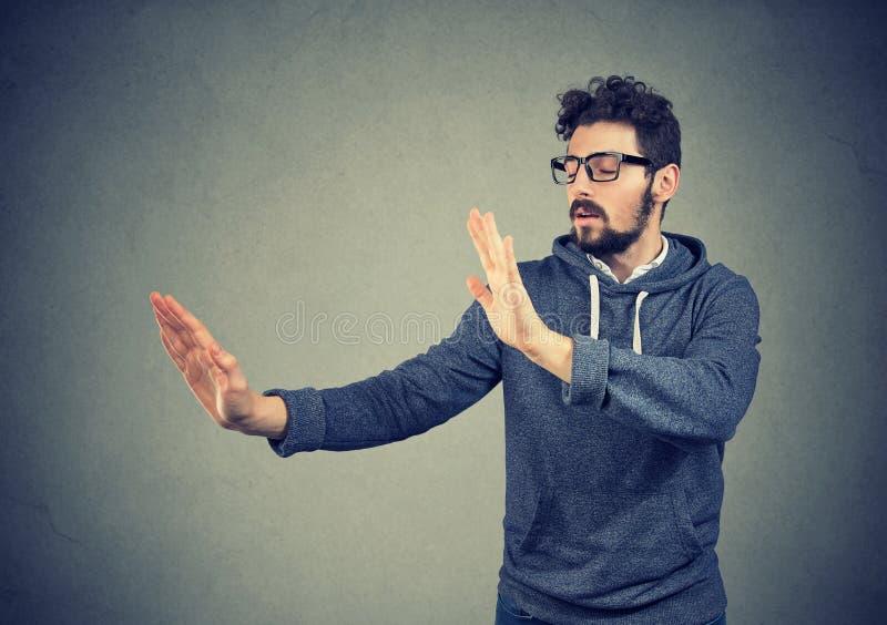 Молодой ослепленный человек протягивая руки и ища в темноте стоковые изображения