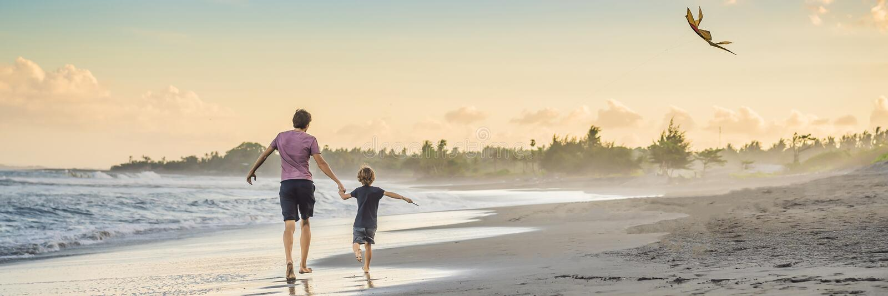 Молодой отец и его сын бежать со змеем на ЗНАМЕНИ пляжа, ДЛИННЫМ ФОРМАТОМ стоковая фотография