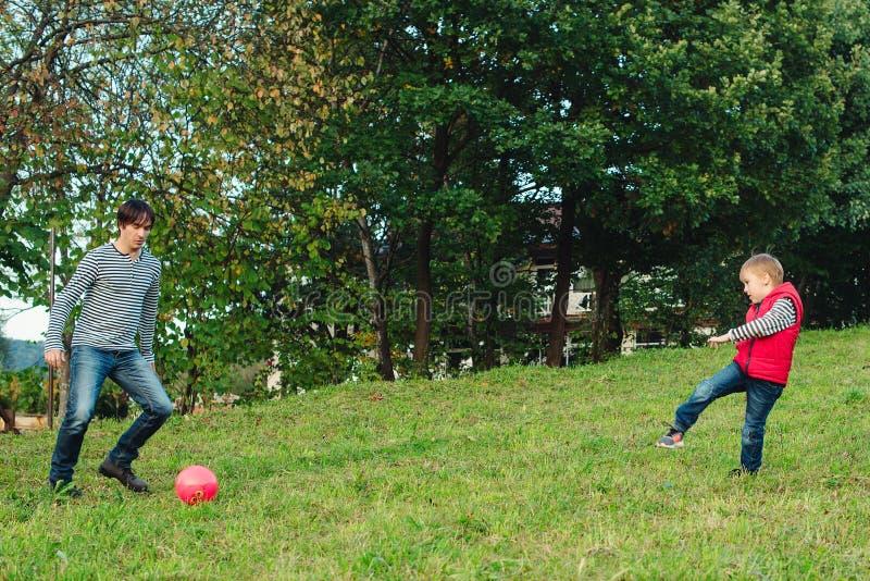 Молодой отец при его маленький сын играя футбол на зеленой травянистой лужайке стоковое фото