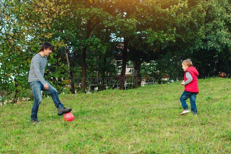 Молодой отец при его маленький сын играя футбол на зеленой травянистой лужайке стоковые фото