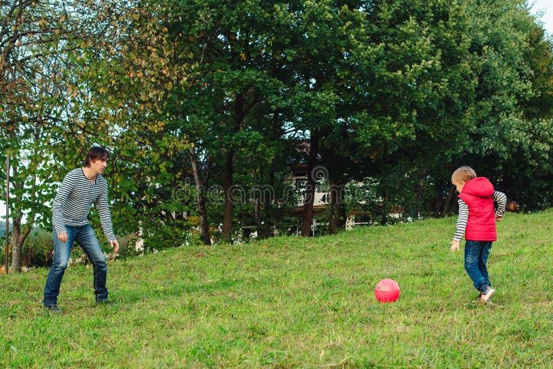 Молодой отец при его маленький сын играя футбол на зеленой травянистой лужайке стоковая фотография rf
