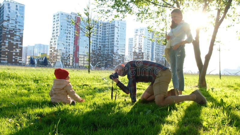 Молодой отец фотографирует молодая дочь в парке на заходе солнца Счастливая семья фотографирует ребенок в природе стоковое фото