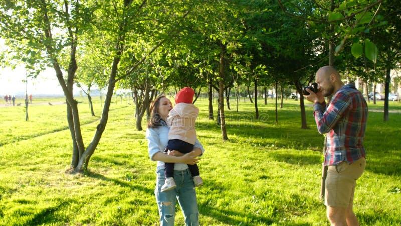 Молодой отец фотографируя мать и дочь играя в парке на заходе солнца Счастливая семья имея остатки и стоковое изображение rf