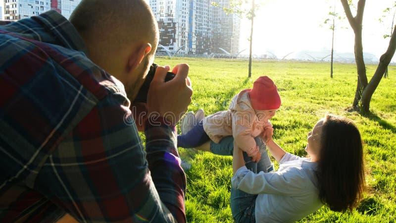 Молодой отец фотографируя мать и дочь играя в парке на заходе солнца Счастливая семья сфотографированная в природе стоковое изображение