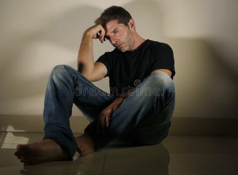 Молодой отчаянный и подавленный плакать человека один сидящ дома пол в смотреть тенистой и драматической студии светлый унылый и  стоковые фотографии rf