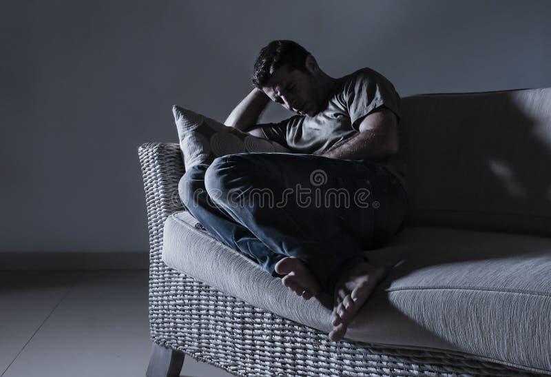 Молодой отчаянный унылый и разочарованный человек горюя дома проблема депрессии кресла софы страдая и плакать кризиса тревожности стоковая фотография