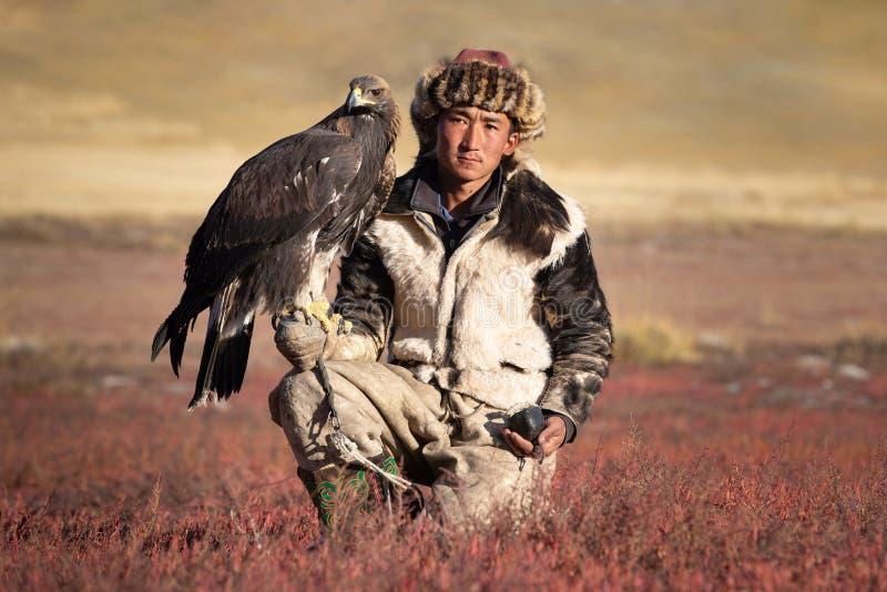 Молодой охотник за орлами Казаха со своим беркутом стоковое изображение