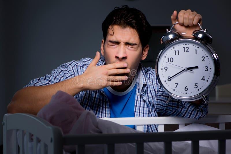 Молодой папа отца спать пока смотрящ после newborn младенца стоковые изображения rf