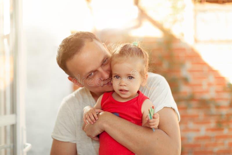 Молодой папа целует его маленькую дочь на щеке стоковые изображения
