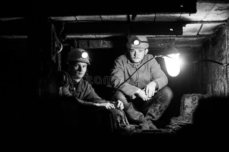Молодой парень в работая форме и защитных шлемах, сидя в низком тоннеле стоковое изображение rf