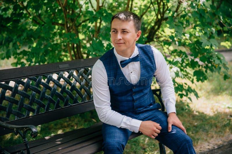 Молодой парень в стильном модном костюме с жилетом и бабочкой сидит в парке на стенде Взгляды groom стоковое изображение