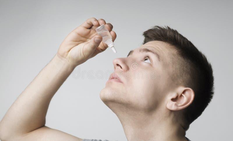 Молодой парень используя падение глаза контакта заболеванием, прикладывая medicament стоковое фото rf