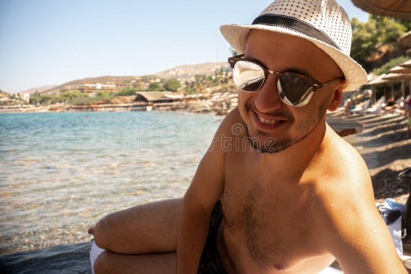 Молодой парень на пляже смотря камеру стоковое изображение