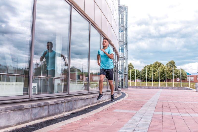 Молодой парень, спорт спортсмен, город лета, бега на jogging утро, открытый космос, окна здания r стоковое фото