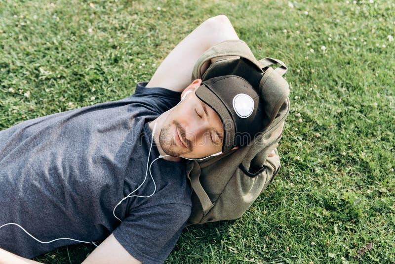 Молодой парень с рюкзаком лежит на траве и слушает к музыке стоковые изображения