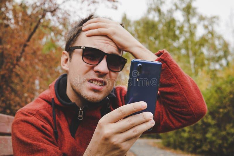 Молодой парень читает новости или SMS на мобильном телефоне и держит его голову с его рукой разочарование сообщения на стоковые изображения rf