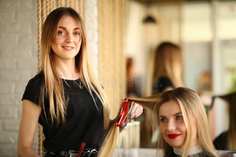 Молодой парикмахер вводя стрижку в моду для клиента девушки стоковое фото